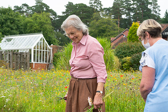 Resident With Carer Picking Flowers
