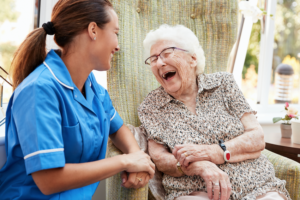 Reasons to work in care - young carer laughing with elderly resident