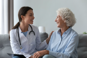 Reasons to work in care - young caregiver smiling with elderly lady
