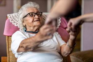 Support for dementia: Elderly lady sat in chair smiling and holding hands with carer
