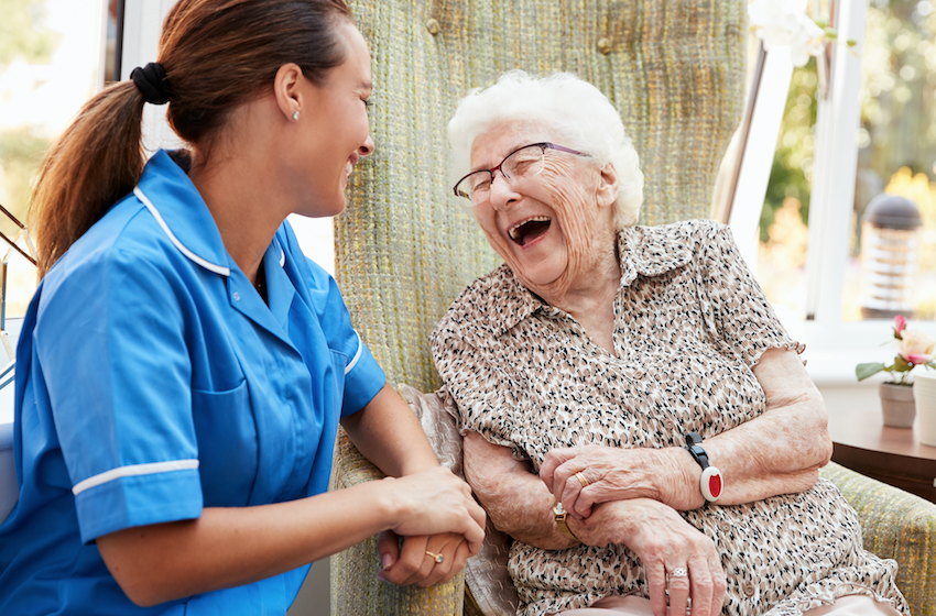 Elderly lady laughing with young carer in residential care setting